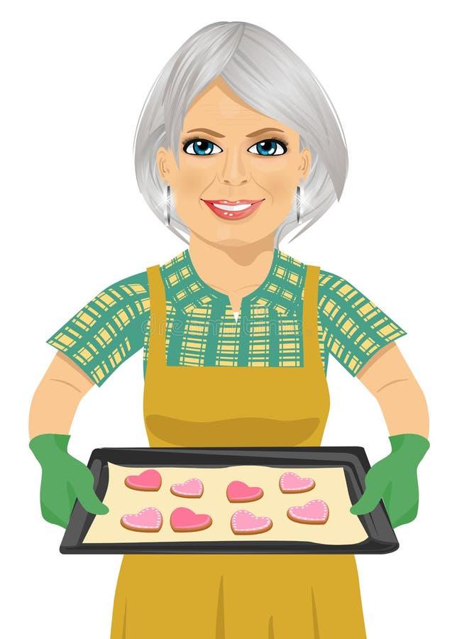 Femme supérieure tenant le plateau de cuisson avec des biscuits de forme de coeur illustration stock