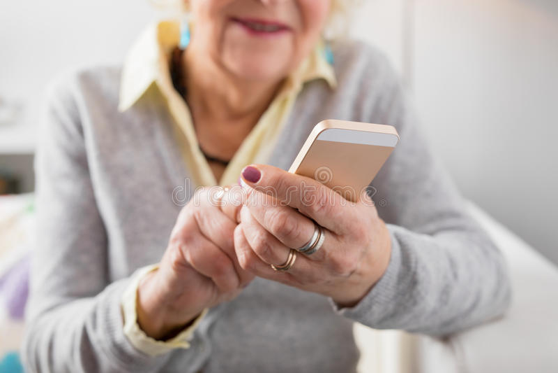 Femme supérieure tenant Smartphone images stock