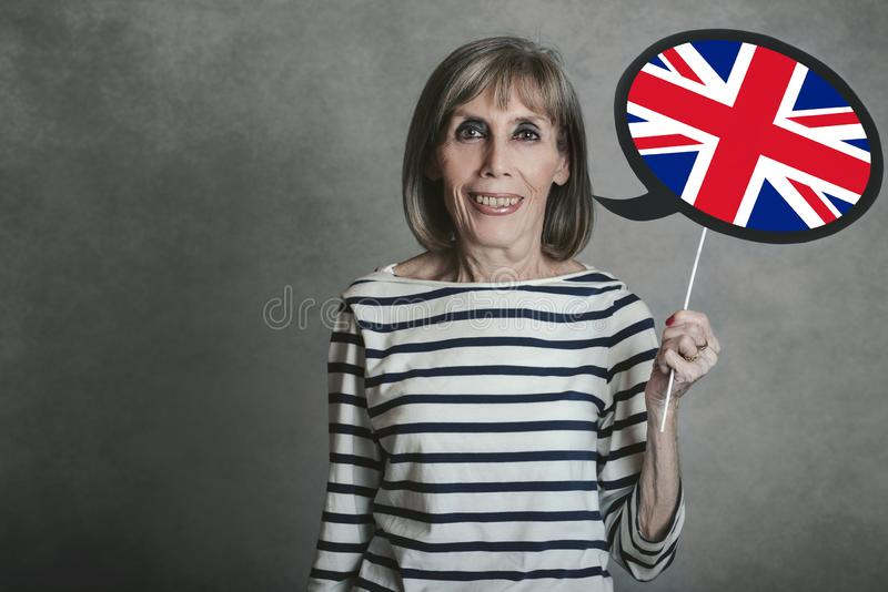Femme supérieure tenant un signe avec le drapeau anglais photos libres de droits