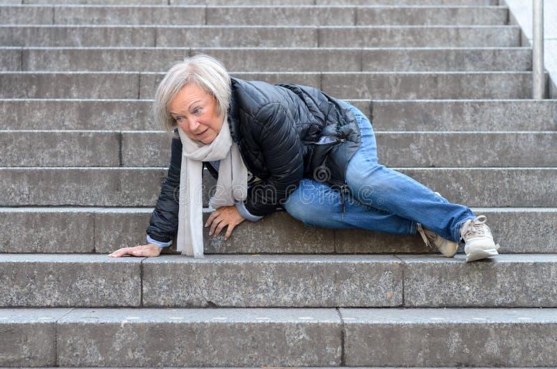 Femme supérieure tombant vers le bas étapes en pierre dehors photo libre de droits