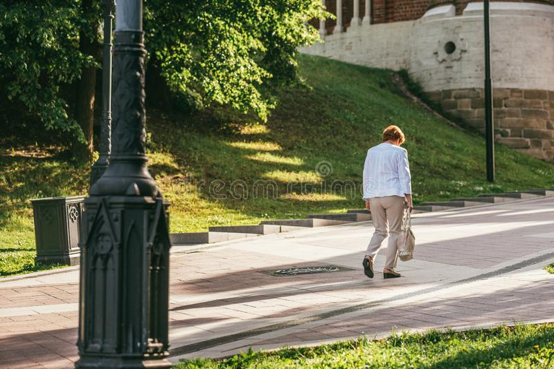 Femme supérieure triste dans une veste blanche et des pantalons beiges marchant avec sa tête vers le bas par le parc allumé par l photographie stock libre de droits