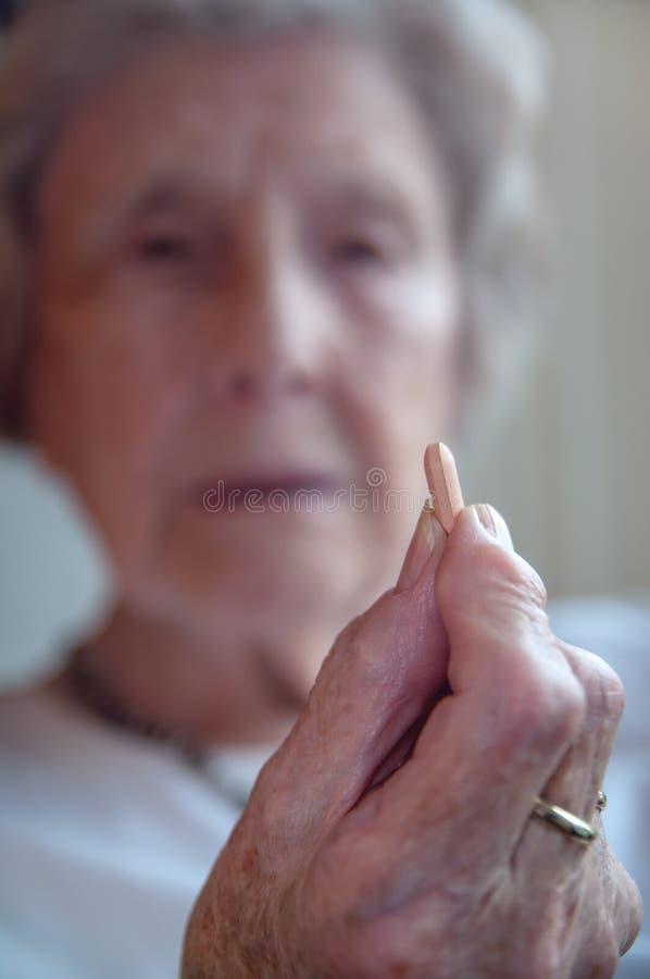 Femme supérieure triste prenant la pilule photo libre de droits