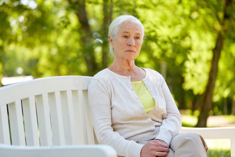 Femme supérieure triste s'asseyant sur le banc au parc d'été images libres de droits