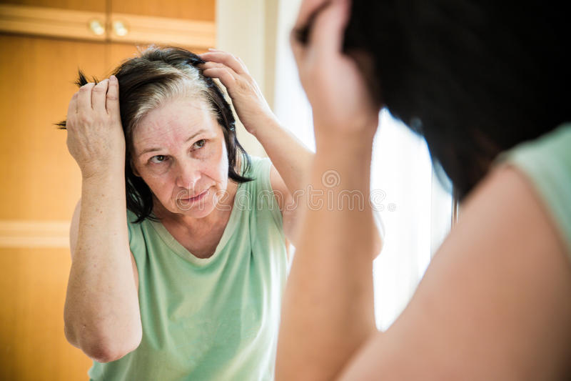 Femme supérieure vérifiant ses racines du poil grises photographie stock