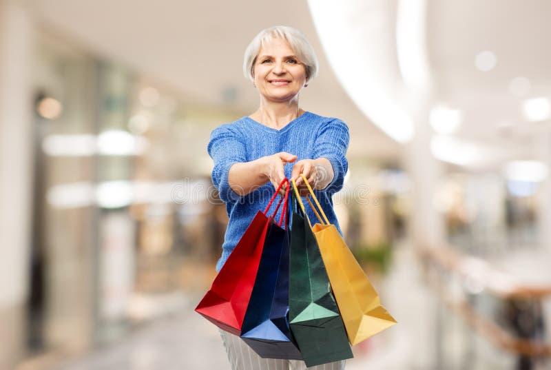 Femme sup?rieure avec des sacs ? provisions au-dessus de mail photos libres de droits