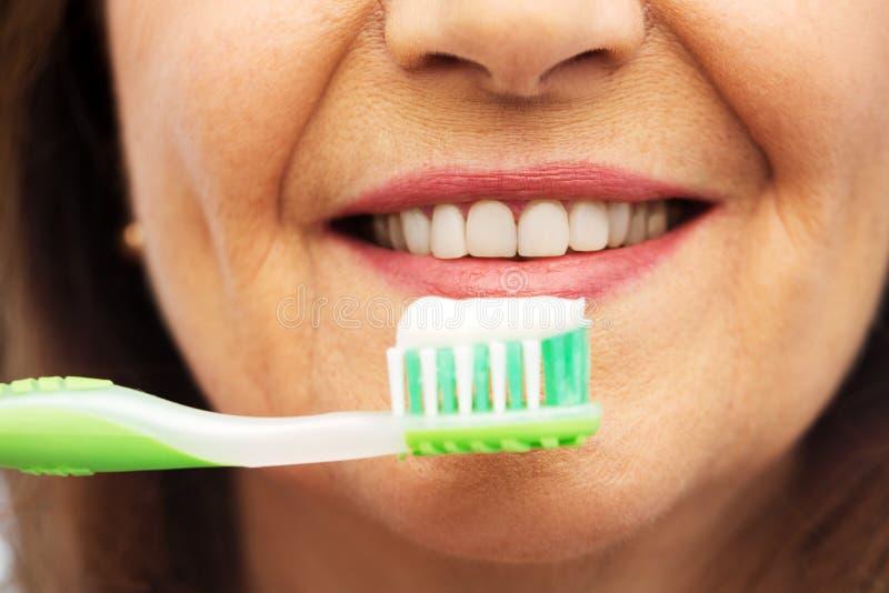 Femme sup?rieure avec la brosse ? dents se brossant les dents photos libres de droits