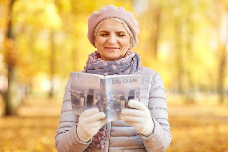 Femme sup?rieure avec le guide de ville au parc d'automne photo libre de droits