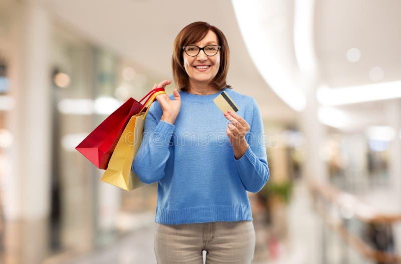 Femme sup?rieure avec les sacs ? provisions et la carte de cr?dit images stock