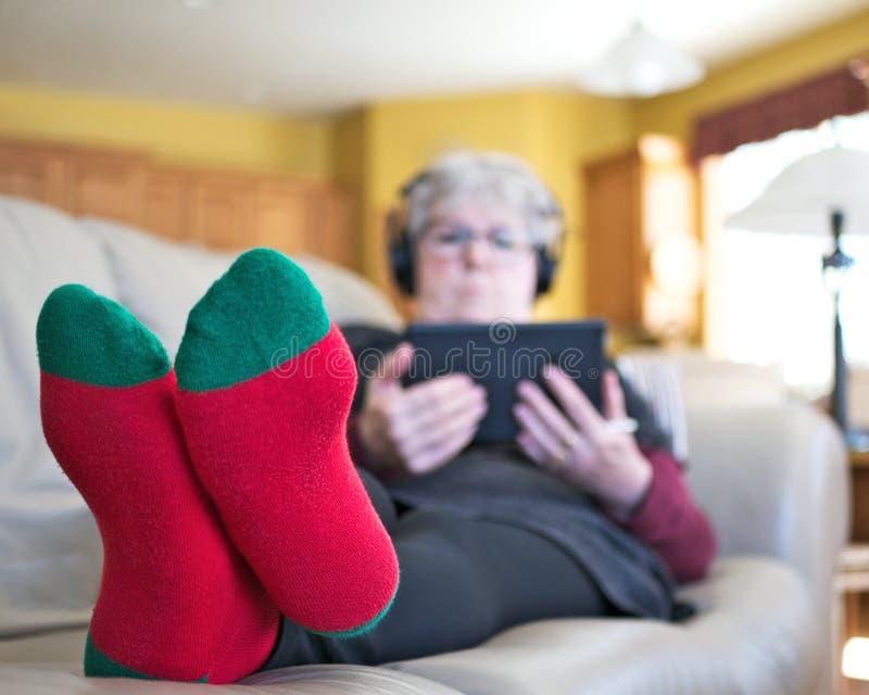 Femme sup?rieure d?tendant sur le sofa ? la maison avec le comprim? et les ?couteurs photos stock
