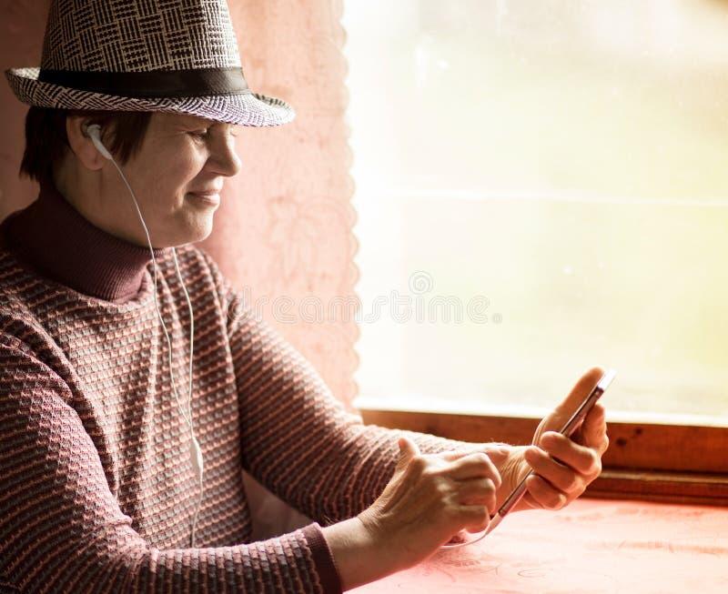 Femme sup?rieure employant l'application mobile sur le smartphone au billet de train et d'achat en ligne photographie stock