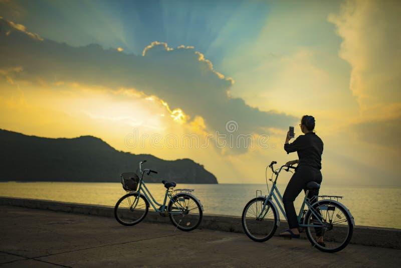 Femme sur la bicyclette prenant une photographie de ciel étonnant de lumière du soleil photographie stock