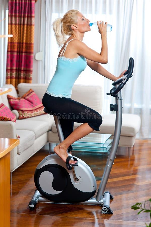 Femme sur la bicyclette stationnaire images stock