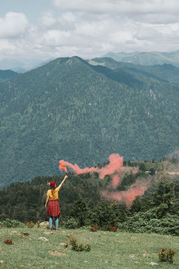 Femme sur la crête de montagne avec la fusée rouge Concept d'inspiration photos stock