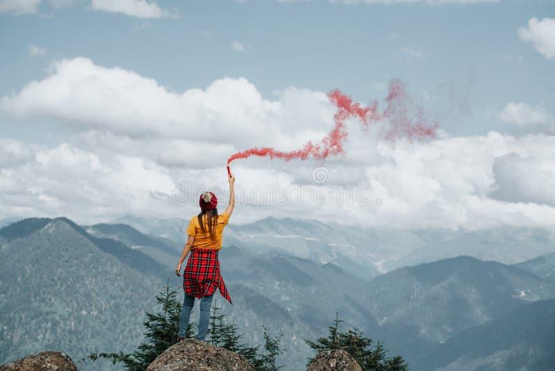 Femme sur la crête de montagne avec la fusée rouge Concept d'inspiration images libres de droits