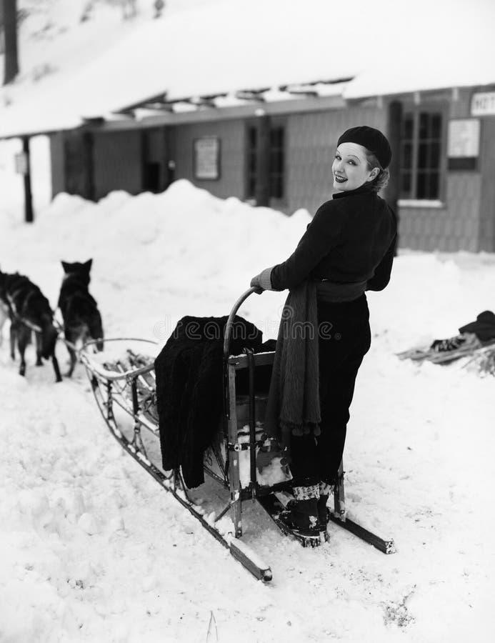 Femme sur la luge tirée par des chiens (toutes les personnes représentées ne sont pas plus long vivantes et aucun domaine n'exist image stock