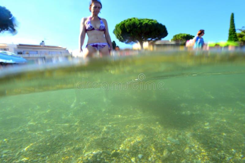 Femme sur la plage allant prendre un bain photo libre de droits