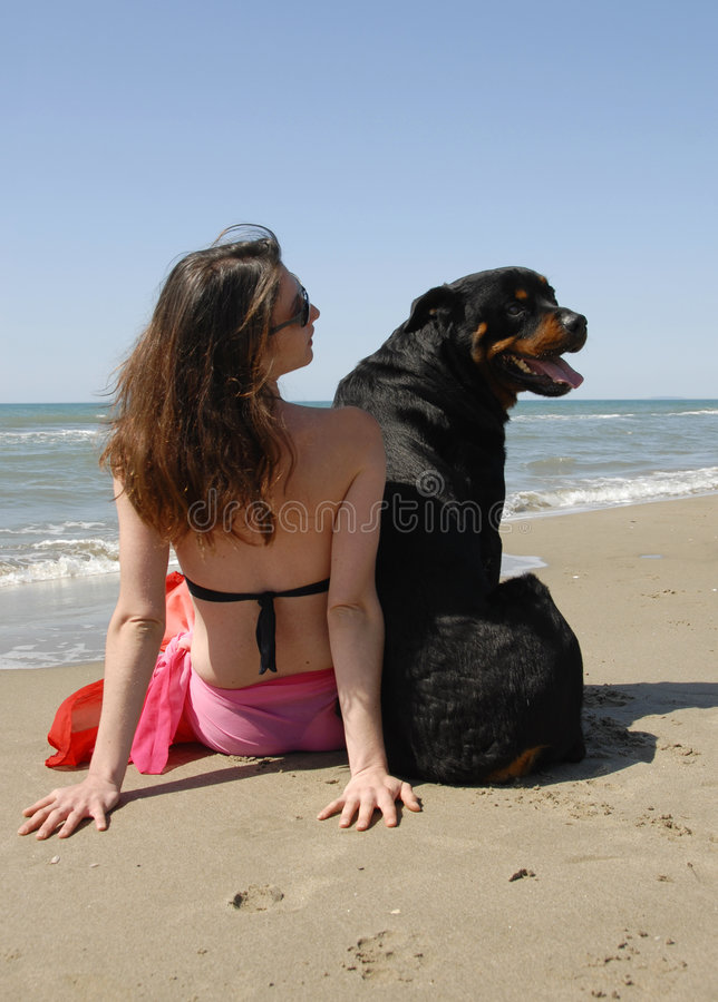 Femme sur la plage avec son rottweiler photo stock