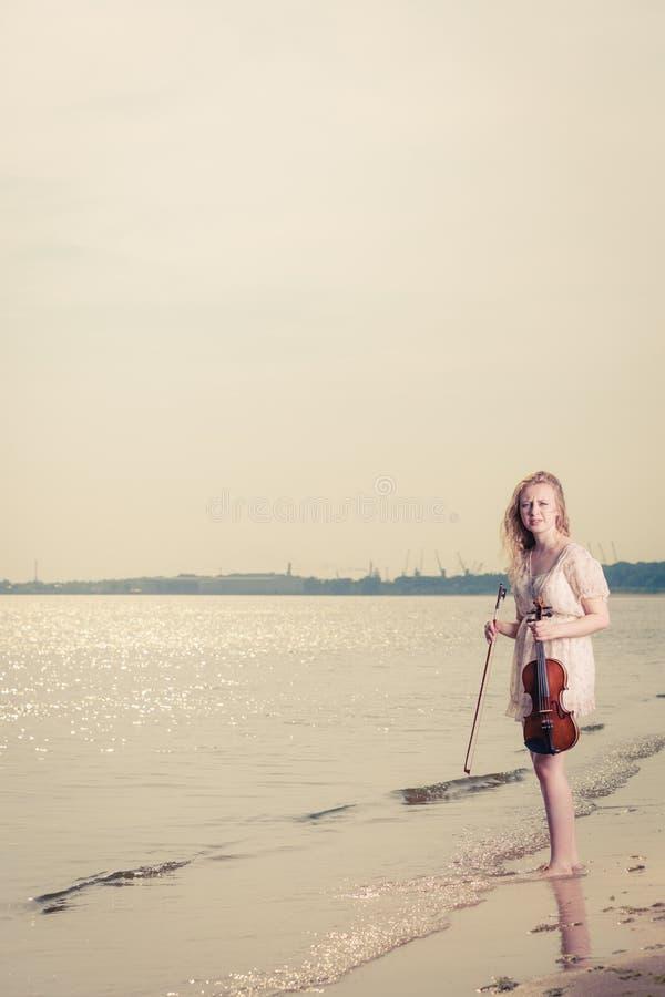 Femme sur la plage près de la mer tenant le violon photographie stock libre de droits