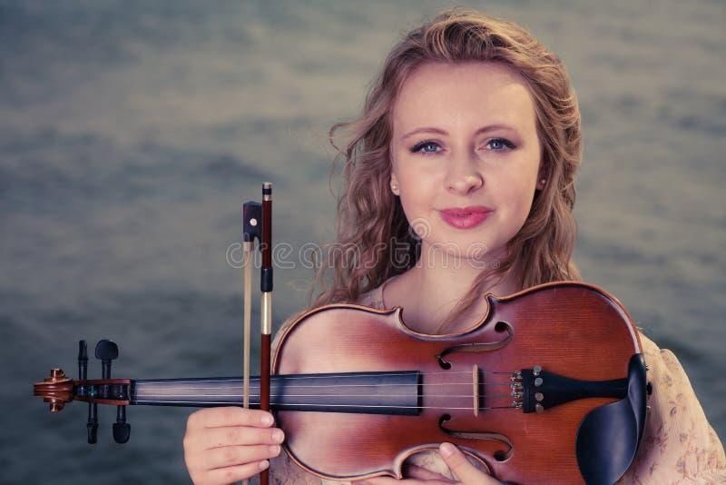 Femme sur la plage près de la mer tenant le violon photo stock