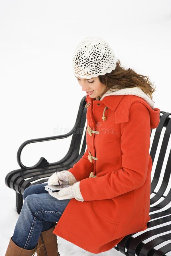 Femme sur le banc avec PDA. photographie stock