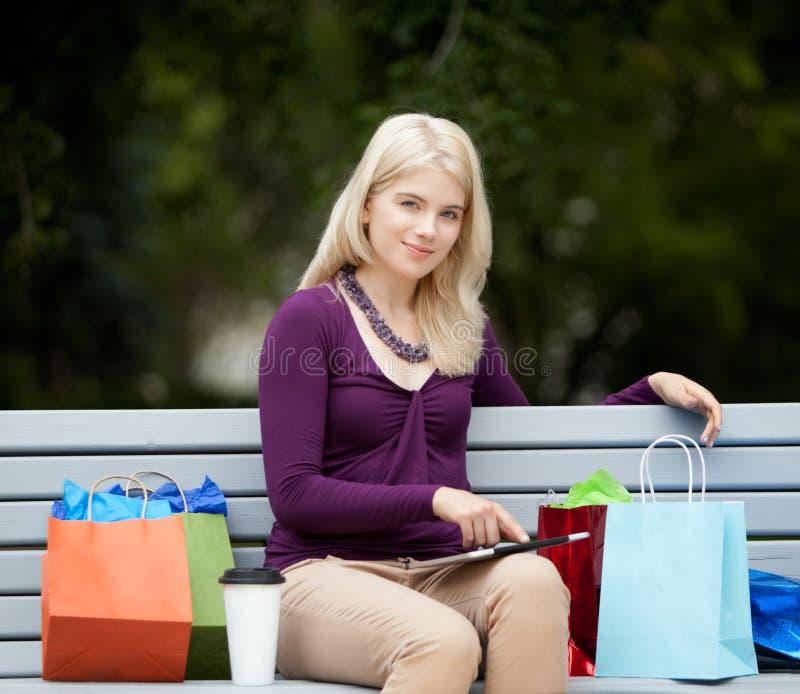 Femme sur le banc de parc avec la Tablette de Digital image stock