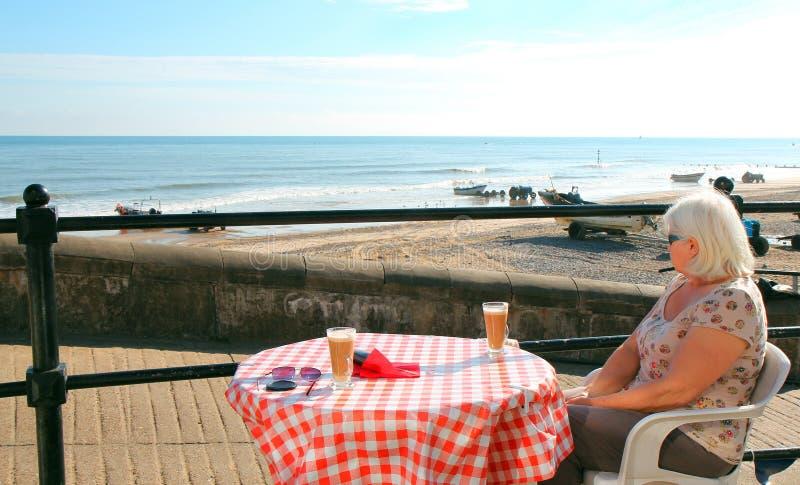 Femme sur le café potable de vacances par l'océan. photo libre de droits