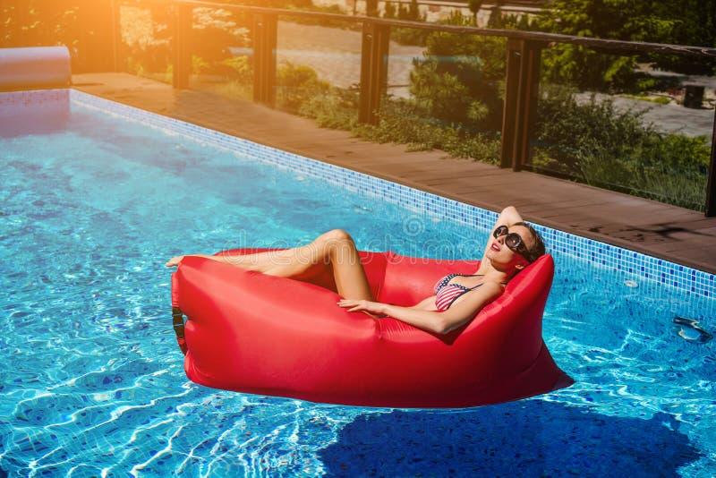 Femme sur le canapé rouge dans la piscine photographie stock