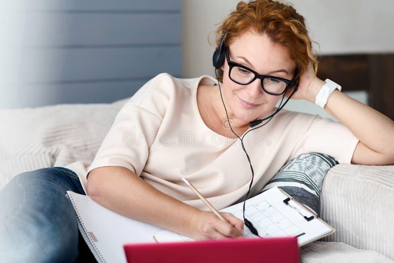 Femme sur le divan avec l'ordinateur portable faisant des notes images stock