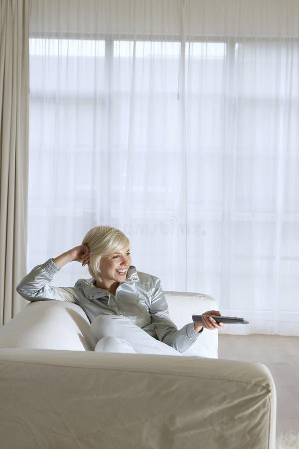 Femme Sur Le Divan Regardant La TV Photographie stock
