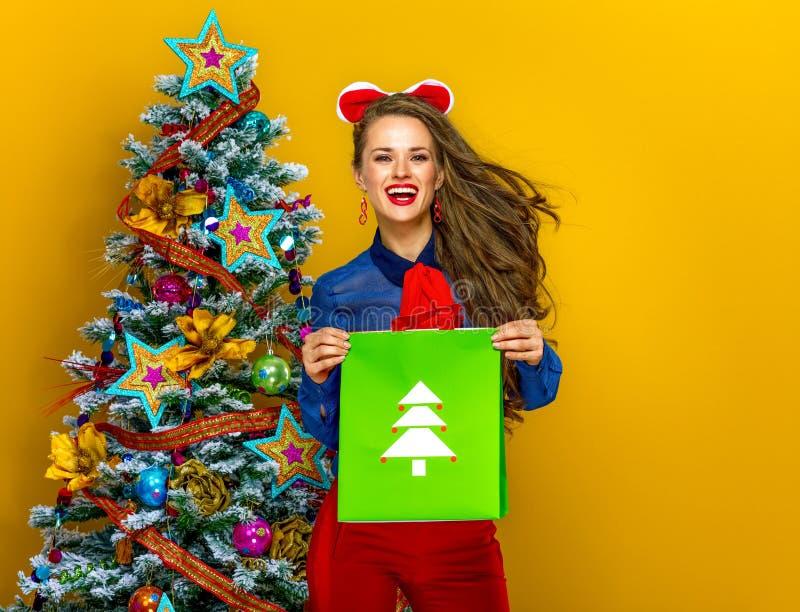 Femme sur le fond jaune tenant le panier de Noël image stock