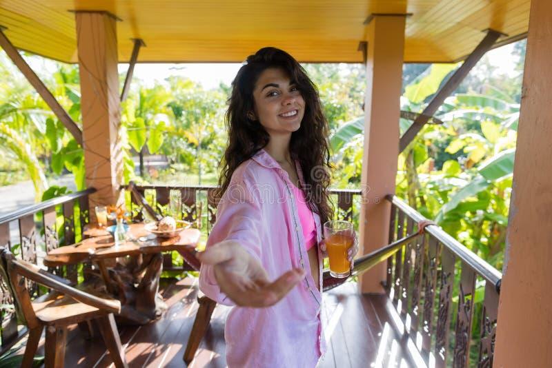 Femme sur le jus d'orange de boissons de main de prise de terrasse d'été, fille de sourire heureuse dans le geste de accueil de m photographie stock
