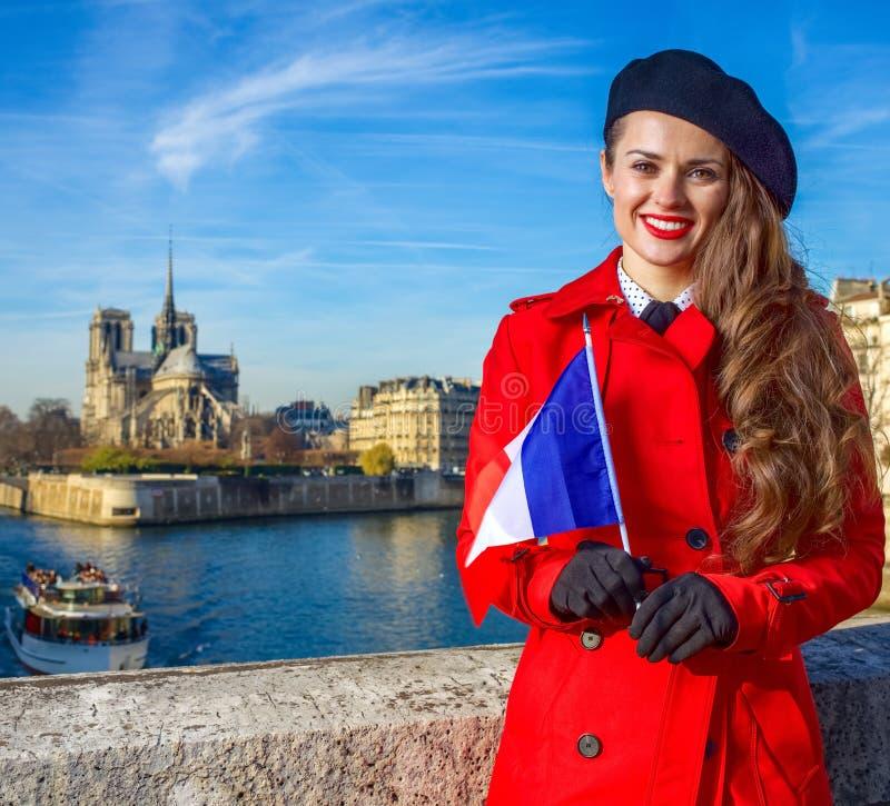Femme sur le remblai près de Notre Dame de Paris avec le drapeau français photographie stock