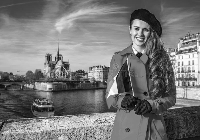 Femme sur le remblai près de Notre Dame de Paris avec le drapeau français images stock
