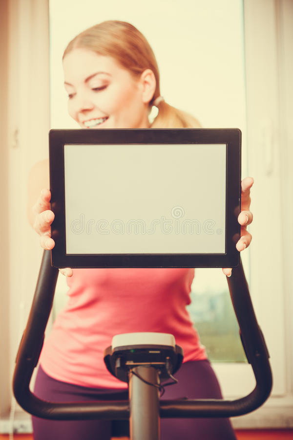 Femme sur le vélo d'exercice tenant le copyspace de comprimé de PC photo libre de droits