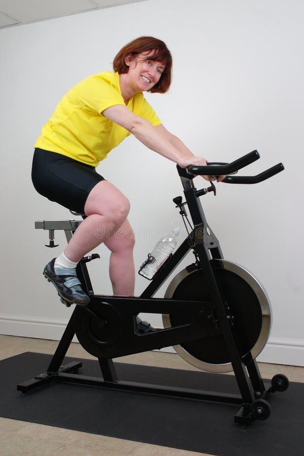 Femme sur le vélo de rotation photo stock
