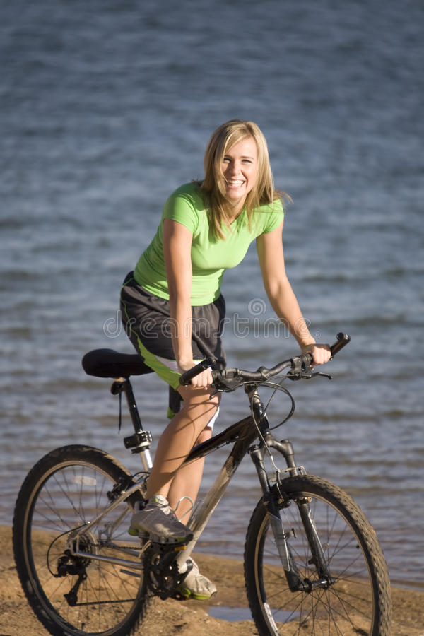 Femme sur le vélo par l'eau photo stock