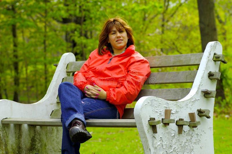 Femme sur un banc photographie stock