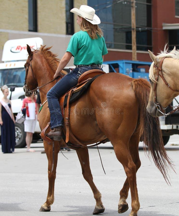 Femme sur un cheval dans un défilé en petite ville Amérique photographie stock libre de droits