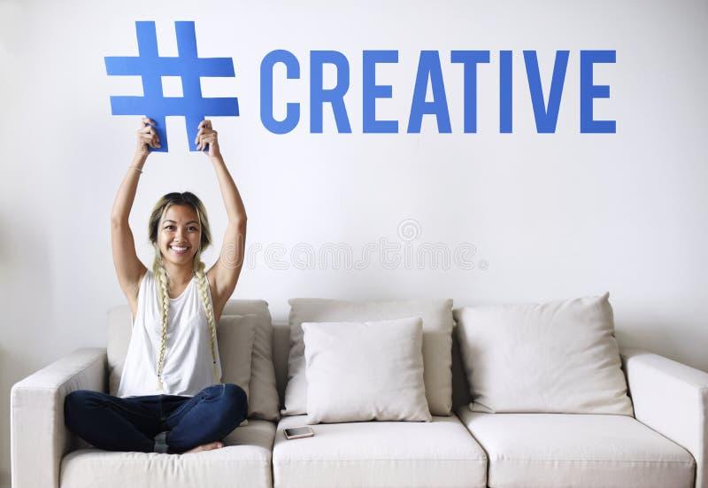 Femme sur un divan tenant un mot photo stock