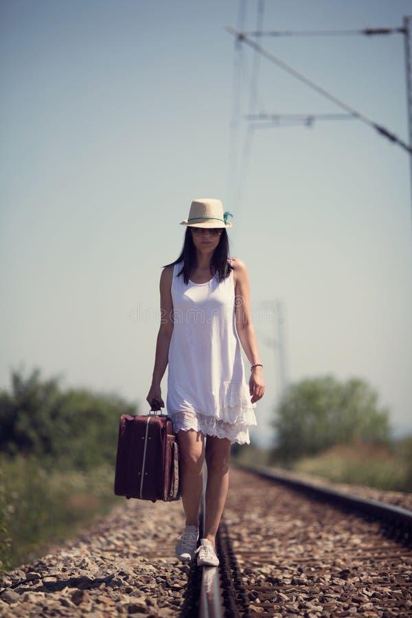 Femme sur un rétro style ferroviaire avec une valise photographie stock