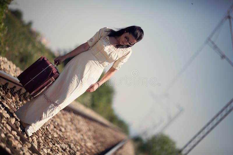 Femme sur un rétro style ferroviaire avec une valise photographie stock libre de droits