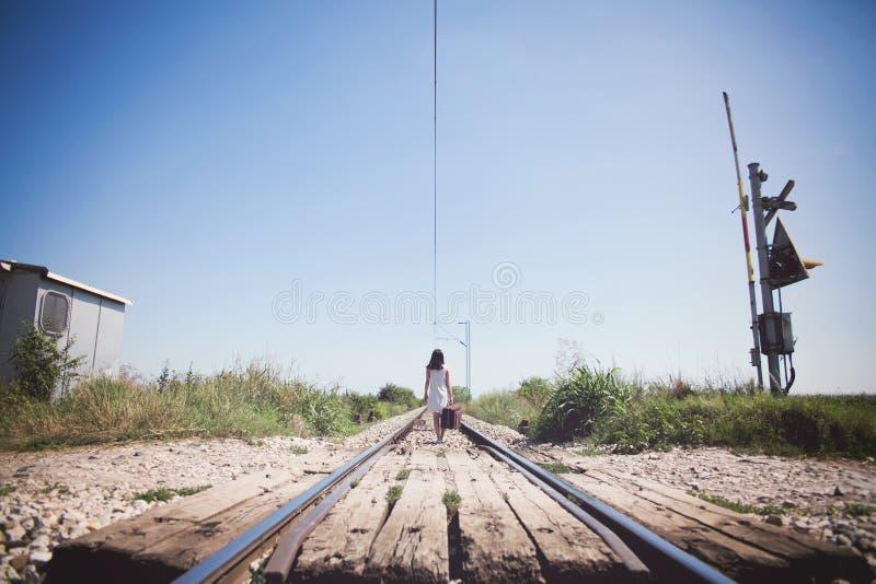Femme sur un rétro style ferroviaire avec une valise image libre de droits