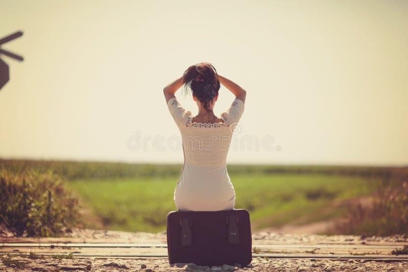 Femme sur un rétro style ferroviaire se reposant sur une valise photos stock