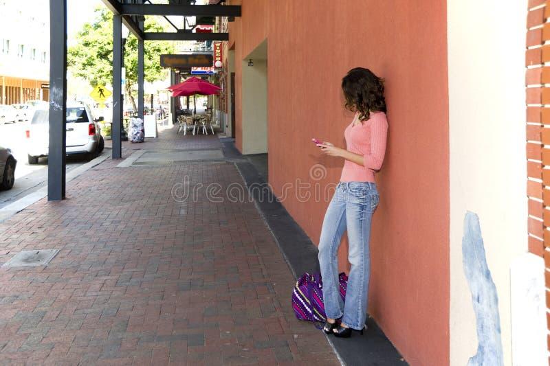 Femme sur un trottoir utilisant un téléphone portable images libres de droits