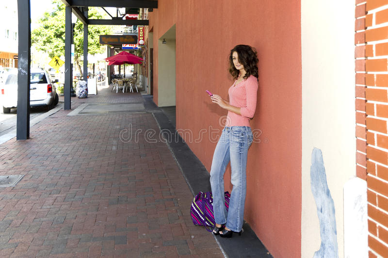 Femme sur un trottoir utilisant un téléphone portable photos stock