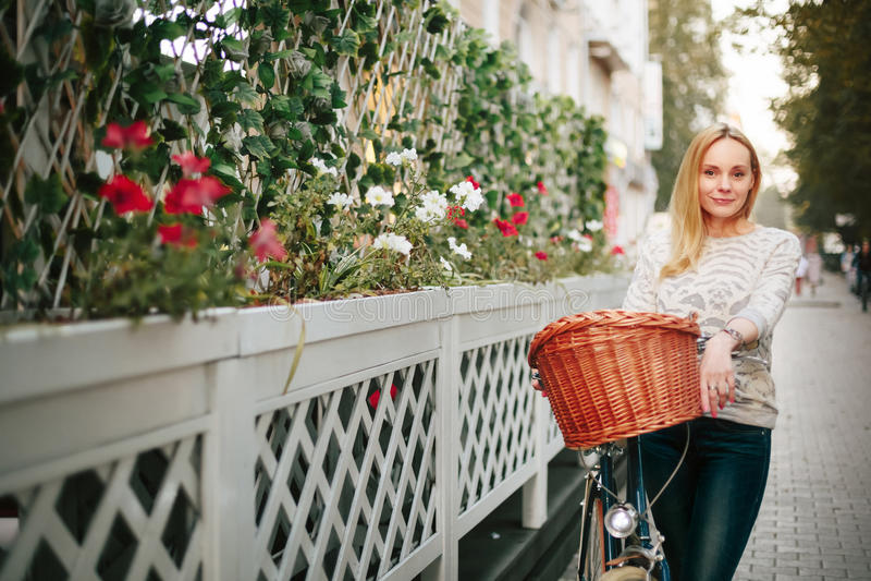 Femme sur une bicyclette de vintage à la rue photo stock