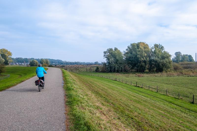 Femme sur une bicyclette sur la digue le long des plaines inondables le long du images stock