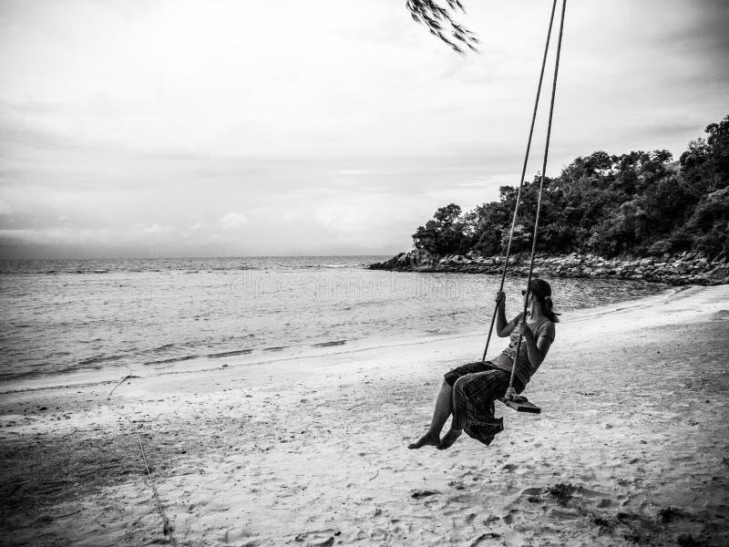 Femme sur une oscillation à une plage tropicale photographie stock libre de droits