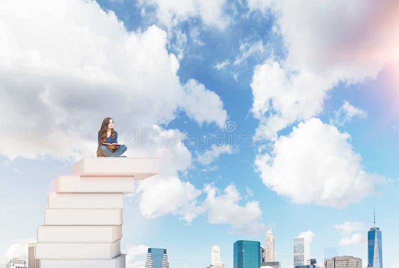 Femme sur une pile des livres photographie stock