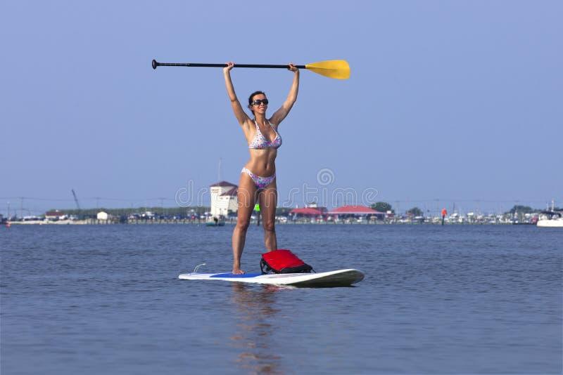 Femme sur une position vers le haut de PETITE GORGÉE de Paddleboard images libres de droits